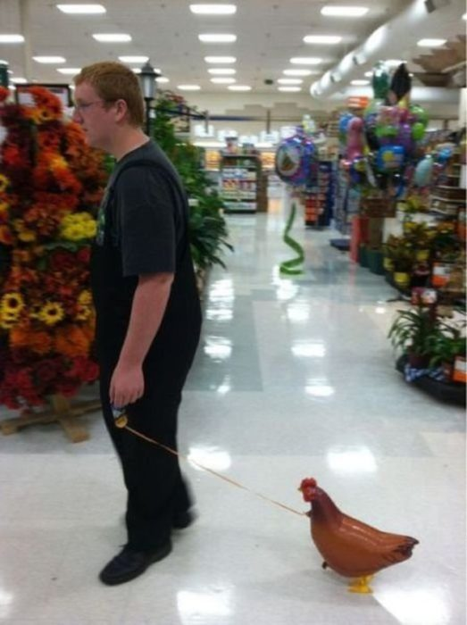 chico con una gallina de plástico