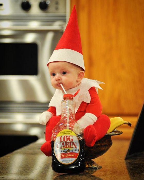 bebé evstido de elfo tomando jarabe de miel