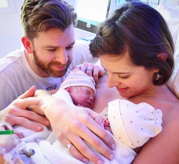 mujer sostiene a sus bebés mientras su esposo los mira