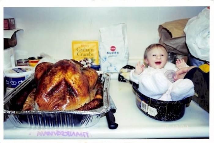bebé pequeña al lado de un pollo asado