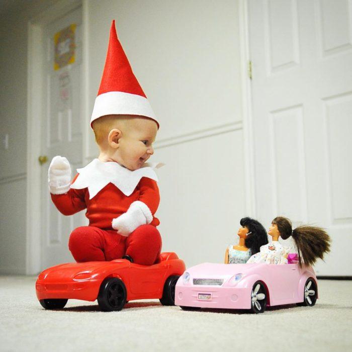bebé vestido de elfo con un carro de muñecas