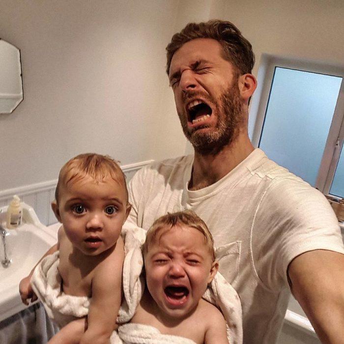 hombre con bebés gemelas llorando