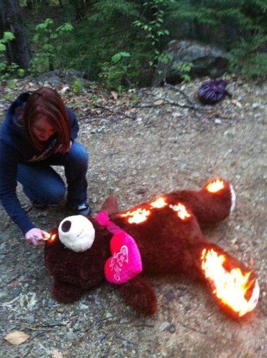 mujer quemando oso de peluche