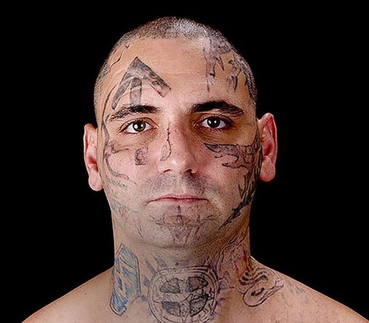 hombre con tatuajes nazi en la cara