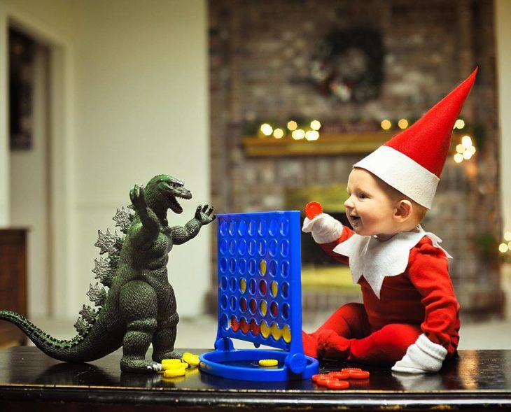 bebé vestido de elfo con godzilla de juguete