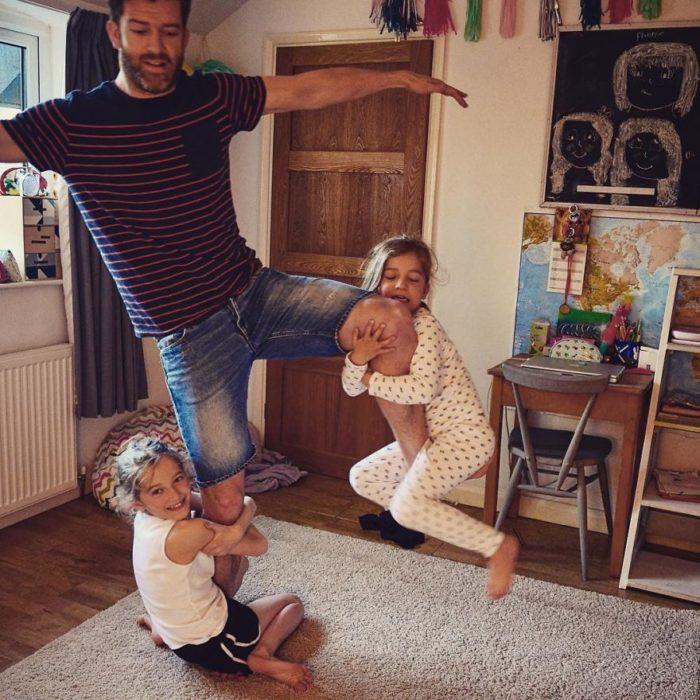 niñas aferradas a las piernas de su papá