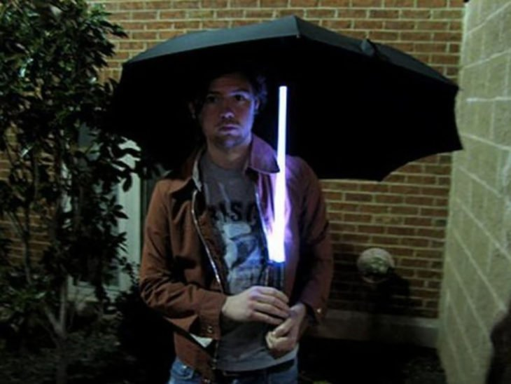 hombre sosteniendo una sombrilla con vara de luz