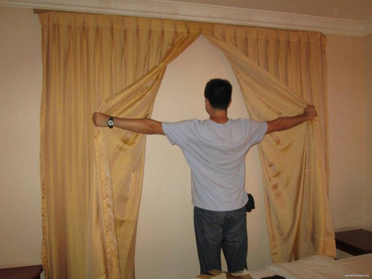 hombre sosteniendo cortinas sin ventana