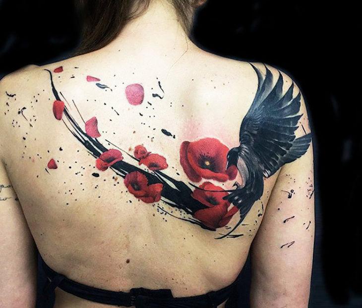 tatuaje de cuervo y flores en la espalda de una chica