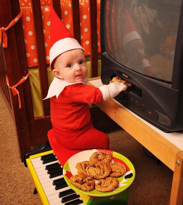 bebé vestido de elfo metiendo galletas a un dvd