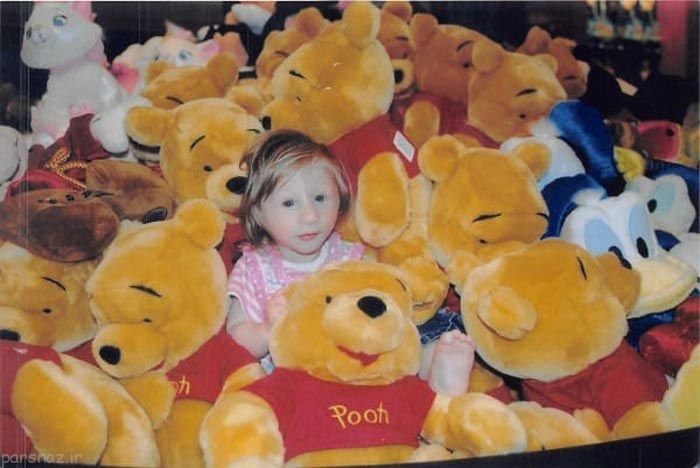 niña pequeñita en medio de peluches de winnie pooh