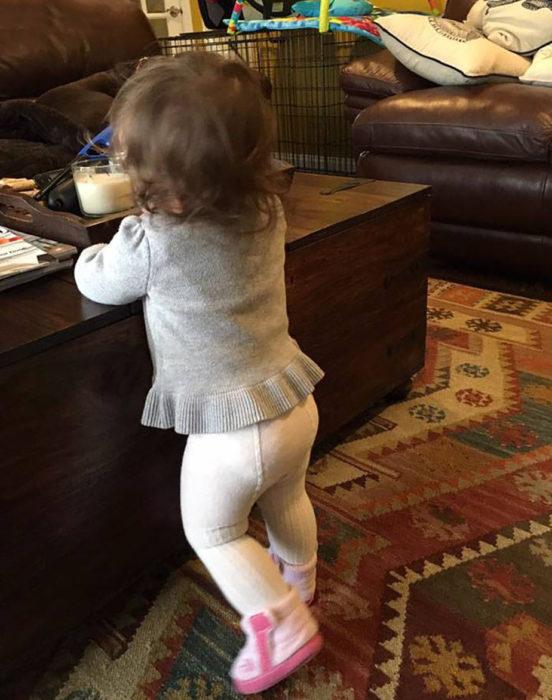 niña con camisa gris y medias blancas
