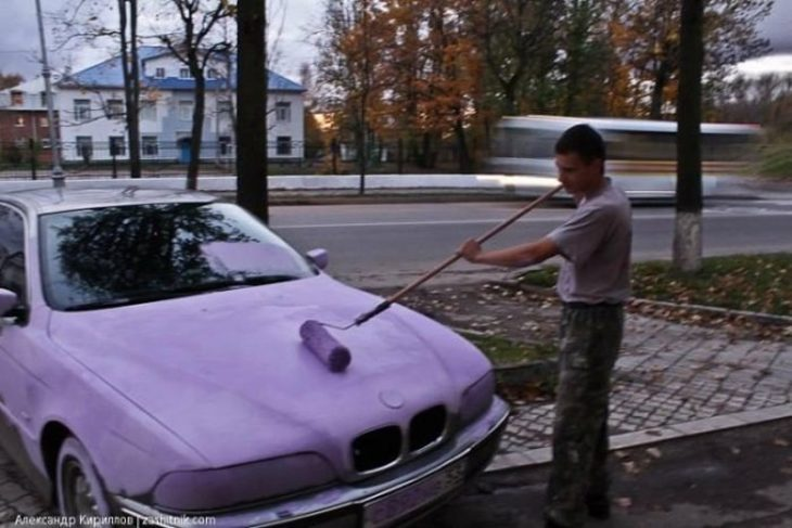 hombre pintando de lila un coche