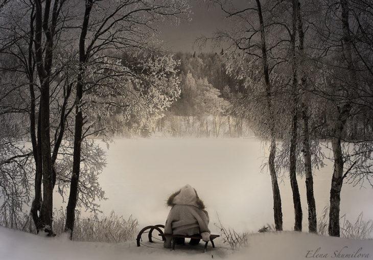 niño sentad en una banca en un paisaje nevado