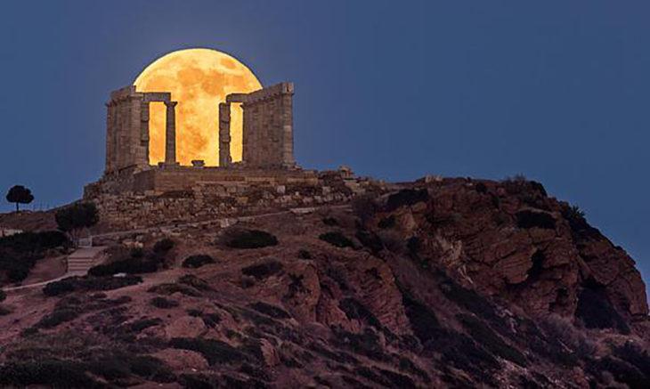 edificio griego en ruinas por el que se ve la luna