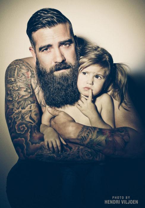 señor tatuado con barba y una niña