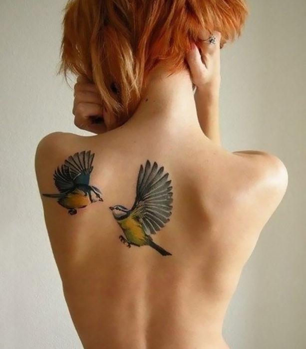 tatuaje de dos aves en espalda de mujer