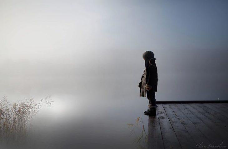 niño al lado de un lago