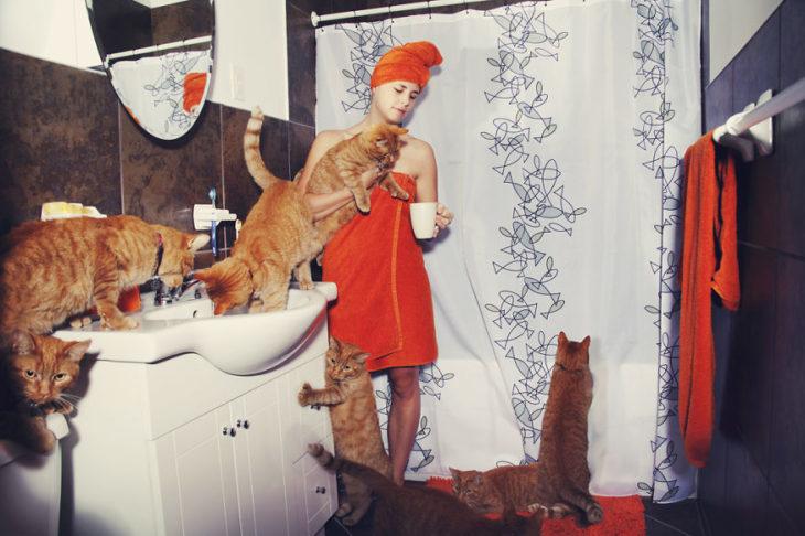 Una persona en el baño junto a sus mascotas