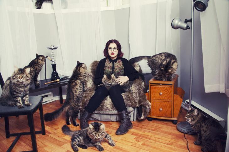 Una mujer que ama a los gatos y tiene muchos