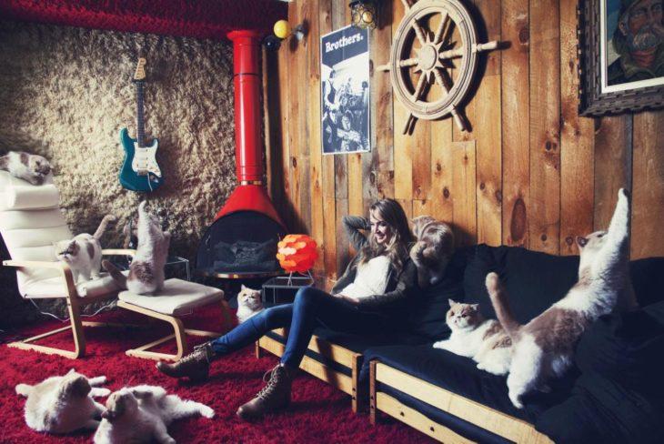 Una joven en la sala de su casa junto a sus mascotas