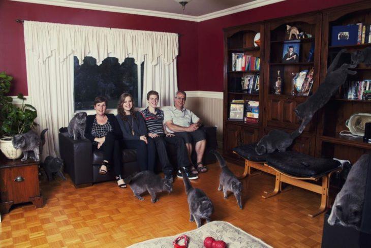 Una familia en la sala de la casa junto a los gatos