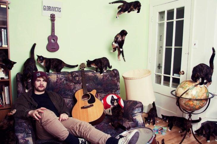 Un chavo en la sala de su casa con su guitarra y sus gatos