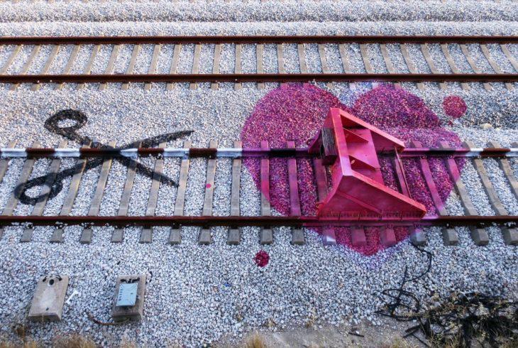 Dibujo de unas tijeras y un corazón sobre las vías del tren