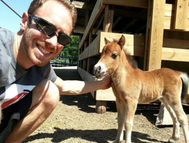 Un chico junto a su caballo miniatura
