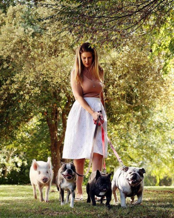 Una mujer paseando con sus mascotas.