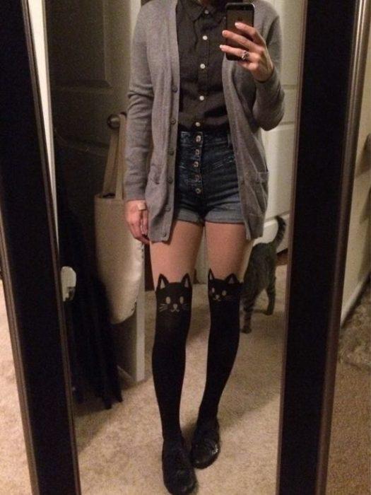 Foto de chica usando calcetas de gatos y su gato está atrás