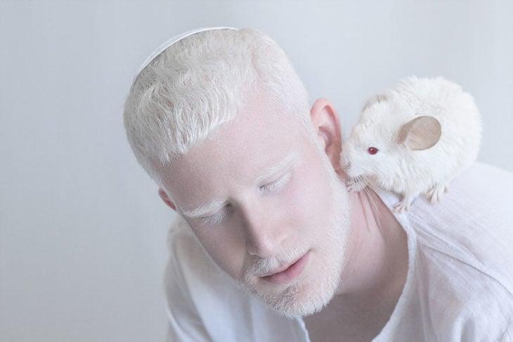 Hombre albino con un ratoncito en su hombro