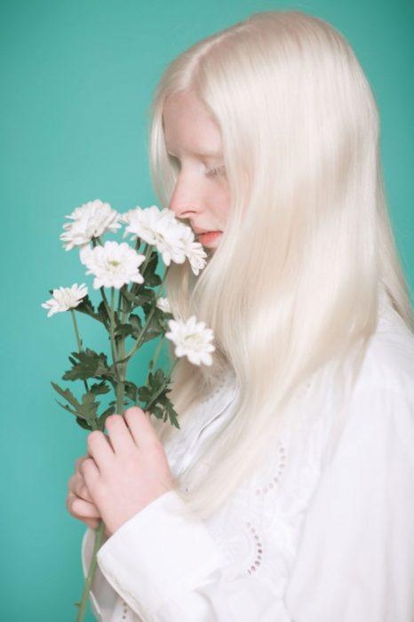 Mujer albina oliendo flores