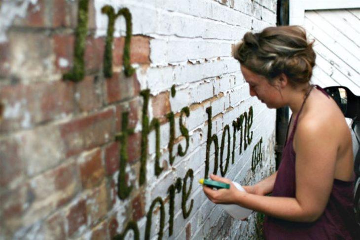 Mujer regando su graffiti de musgo