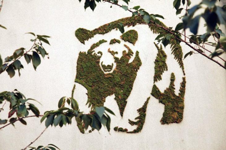 Oso en la pared pintado con musgo