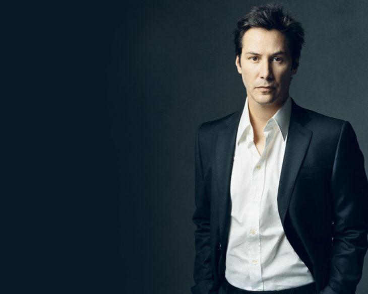 Keanu Reeves fondo negro y traje negro