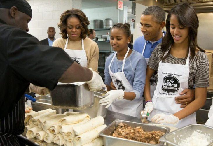 Michelle Obama y familia sirviendo comida
