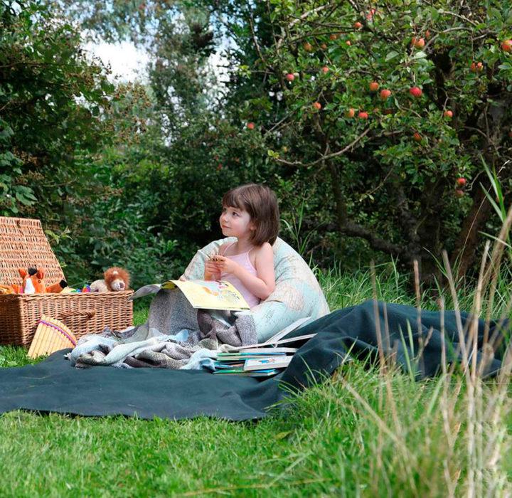 Iris Grace sentada sobre el pasto pintando