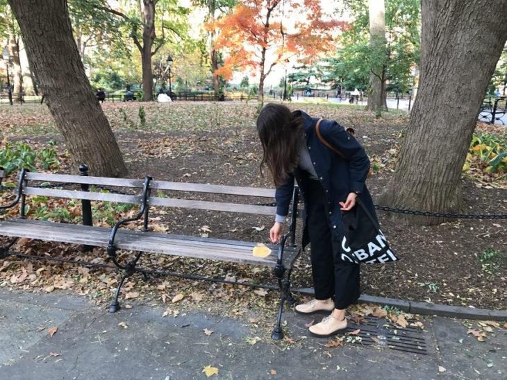 Una jóven colocando hojas con poesía en los parques