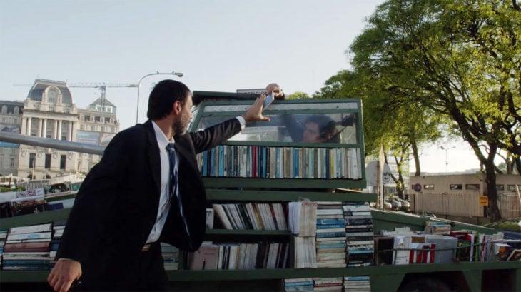 Hombre recibiendo un libro regalado por parte de un artista