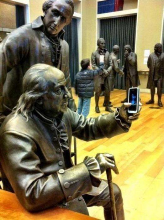 estatua con un celular