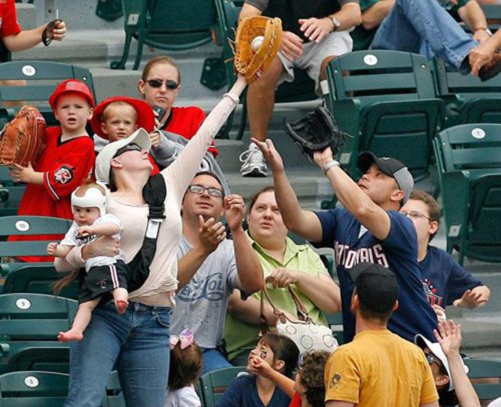 mujer con bebe atrapa una bola de béisbol