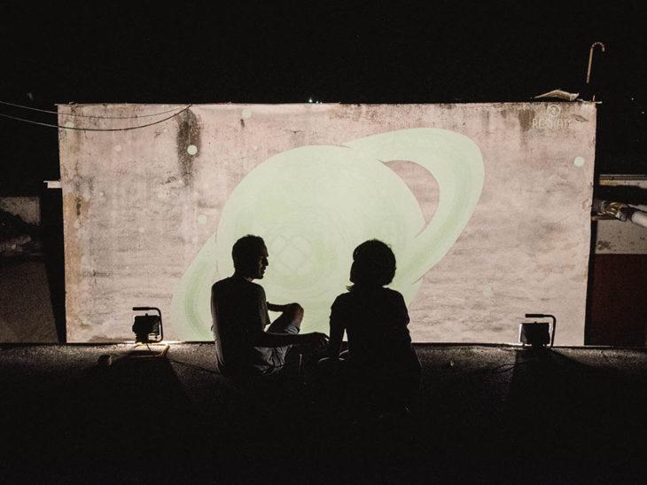 hombre y mujer sentados frente aun mural de saturno
