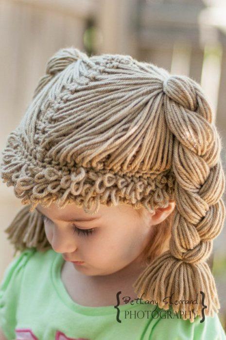 niña con peluca de estambre trensada