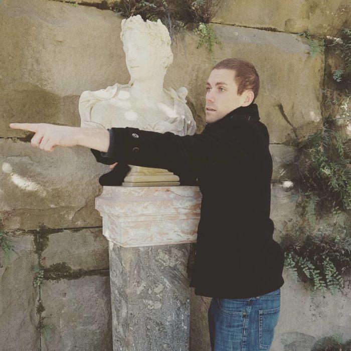 hombre posa al lado de un busto romano
