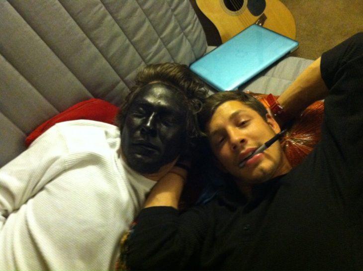 dos chicos recostados, uno con la cara pintada negra y el otro con el plumón entre los dientes