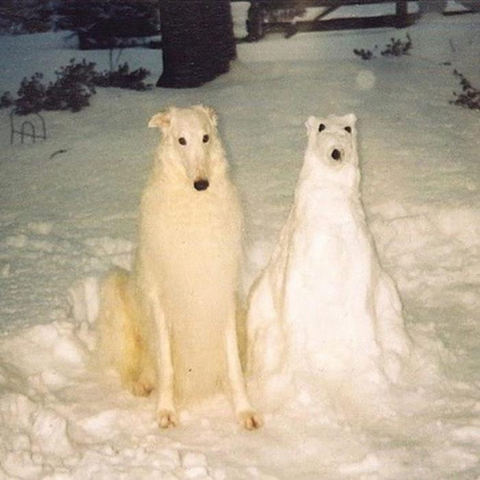 perro al lado de una escultura de nieve de él mismo