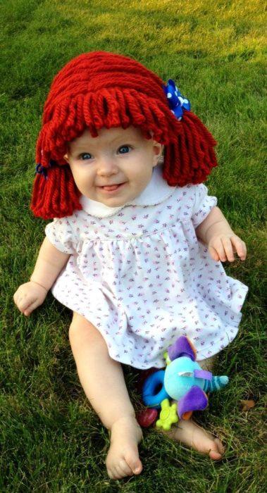 niña con peluca de dos colitas hecha de estambre