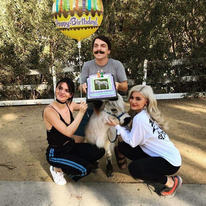 hombre se edita al lado de kendall jenner y kilye sosteniendo un pastel