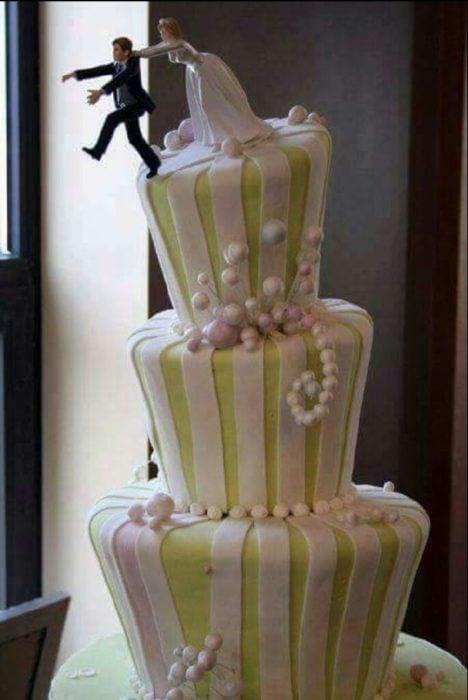 pastel de boda en el que el muñeco novio trata de escapar de la muñeca novia